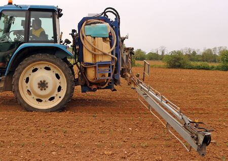 Long boom sprayer, trailed by a tractor, prepares to spray pesticides on a field with sprouts in a gray early spring day