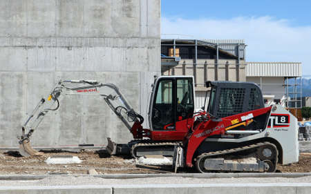 Udine, Italy. May 17, 2020. Brand new Takeuchi mini excavator and mini bulldozer at work in a construction site during a redevelopment of an industrial area