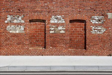 Brick wall with walled windows and natural stones insertions and a white concrete sidewalk in front. Background for copy space.