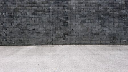 Grunge concrete wall made of squared weathered blocks. Asphalt road in front. Background for copy space.