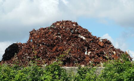 Large heap of rusty ferrous materials and iron abandoned in the countryside. Environmental issue.