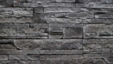 Black stone cladding wall made with different block panels stacked Background and texture.