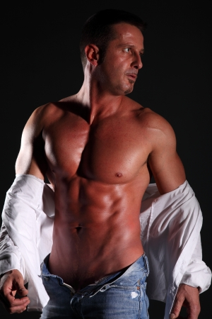 Portraits of nude muscular man in white shirt and jeans photo