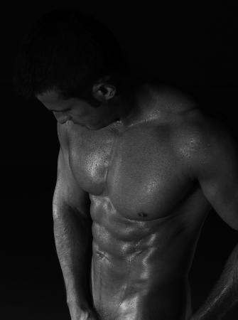 seminude: seminude muscoloso uomo bagnato su sfondo nero Archivio Fotografico