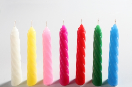 fuchsia color: seven colored candles on white background