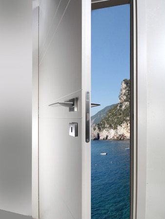 new entry: white door open to the sea coast sunset