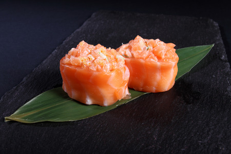 seaa: stew salmon on green leaf, black background