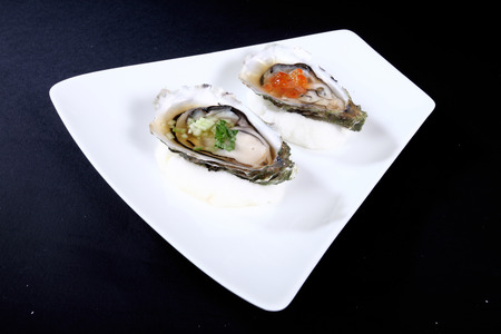 seaa: white plate with two oysters on a black background