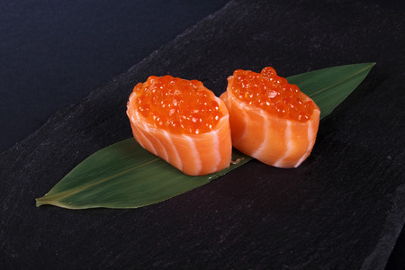 seaa: rolls with fish eggs on leaf green, black background