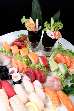 round plate of sashimi and sushi with mixed vegetables and ice
