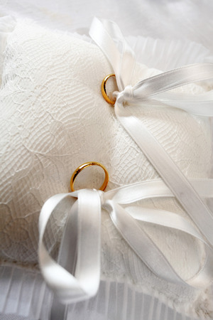 anillos boda: yellow wedding rings on white pillow with tassels