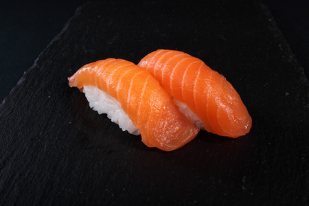 seaa: mixed sushi on white plate, black background