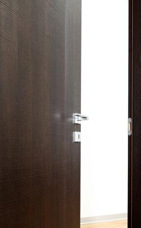 puerta abierta: puerta oscura abierta, con el mango, sobre fondo blanco