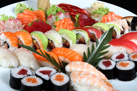 close-up sushi and sashimi mixed on round white plate on a black background Stock Photo