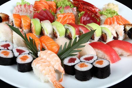 Close-up sushi et sashimi mélangé sur la plaque blanche ronde sur un fond noir Banque d'images - 44696872