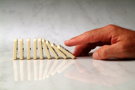 pushed: row of dominoes pushed by hand, on neutral background Stock Photo