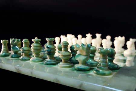 target thinking: chessboard and alabaster chess on a black background