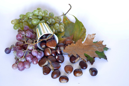 autumn leaves, chestnuts and grapes with chestnuts and grapes, dried leaves, white background