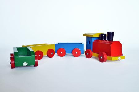 Houten trein met locomotief en wagens, geassembleerd met gekleurde blokken, geïsoleerd op een witte achtergrond. onderdeel van een serie
