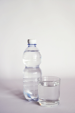 a transparent glass full of water. close to a bottle of mineral water. Imagens
