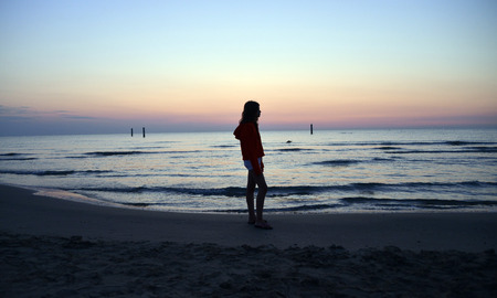 a girl standing on the beach with her arms outstretched as the sun rises, backlighting
