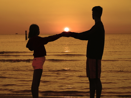 a boy and a girl on a beach playing with the sun on the horizon, backlighting