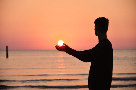a boy in backlight on a beach holds the rising sun in his hands Banco de Imagens