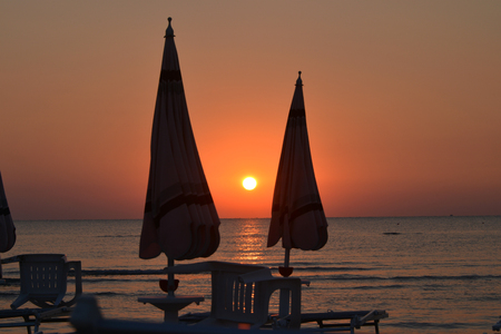 umbrellas on the beach at sunrise, backlighting