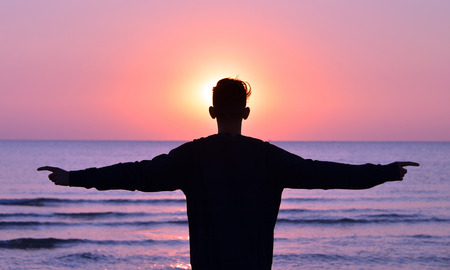 a boy standing on the beach while the sun rises, backlighting