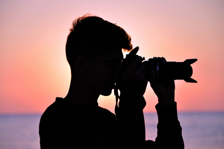 a boy takes pictures on the beach while the sun rises, against the light