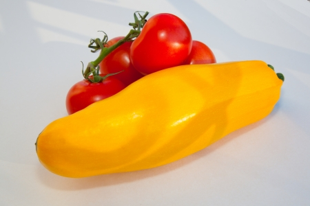 A fresh yellow cucurbit and tomatoes on a branch