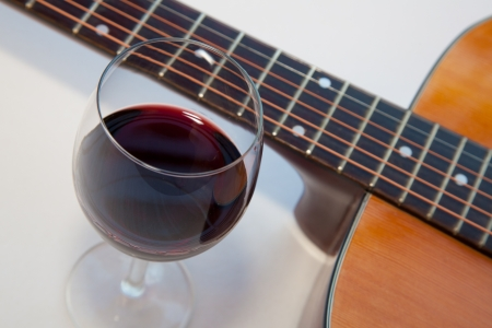 Glass of red wine and a part of acoustic guitar. White background with shadows. photo