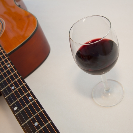 Glass of red wine and a part of acoustic guitar  White background with shadows