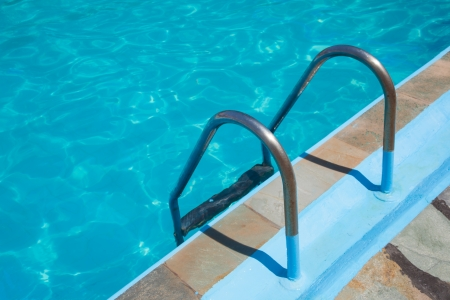 The metal ladder to the blue swimming pool