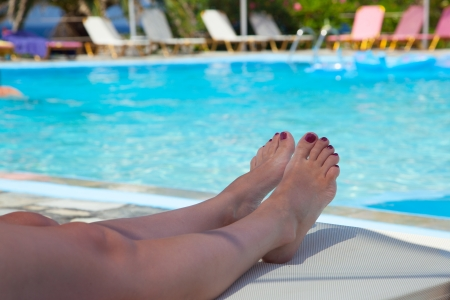 Legs of a young woman. In the background of blue swimming pool