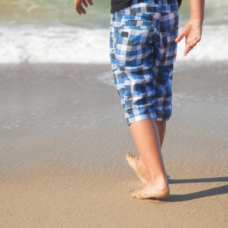 A boy walks on the beach. In the background of the sea. Sand. Stock Photo