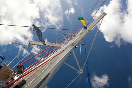 Sailboat mast on the cloudy blue sky  No sail  A lot of ropes  Black and color flag means nothing