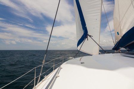 Part of white yacht with sail on the open ocean  Nobody  Cloudy blue sky  Stock Photo