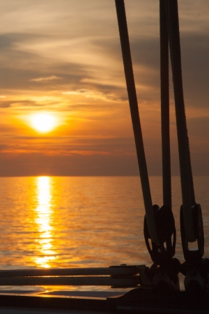 Sailboat mast on the sunrise sky  No sail  A lot of ropes