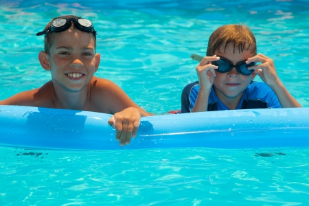 Two happy boys in the swimming pool. Blue water. Brothers