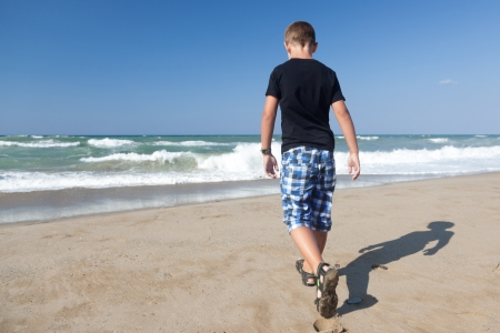 A little boy walking alone on the beach Stock Photo