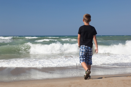 lonely boy: A little boy walking alone on the beach. Blue sky and brown sand. Waves.