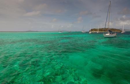 Several yachts, amazing green water, small caribbean island. Tobago cays. Southern Grenadines.