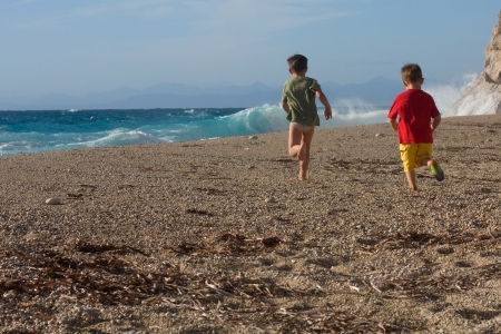 Two happy boys brothers run along the beach turned away back Stock Photo