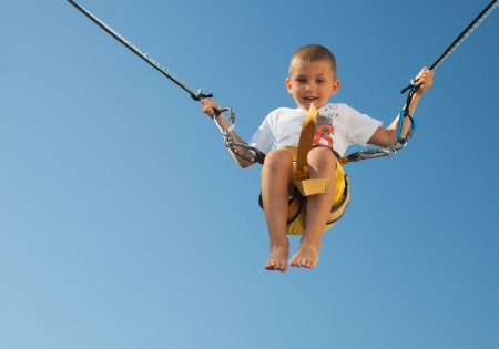 Very happy small boy jumping ont the rope  Blue clear background with free space  Stock Photo