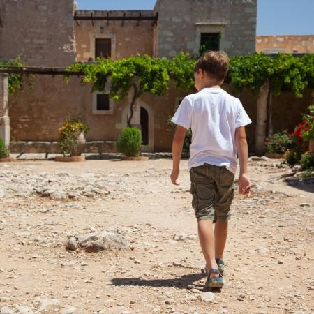 niños caminando: Pequeño niño caminando cerca del viejo monasterio de Agia Triada Grecia Creta
