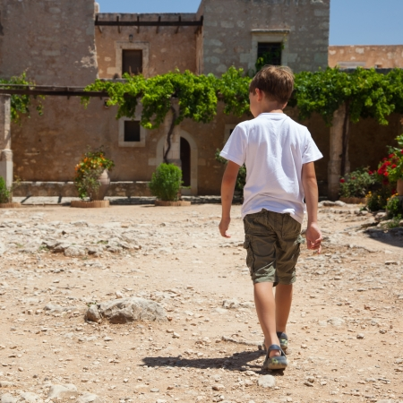 Small boy walking near old Greece Monastery of Agia Triada  Crete  Stock Photo