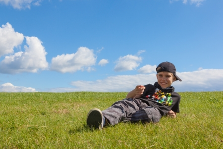 The boy lies on meadow  Blue sky with clouds