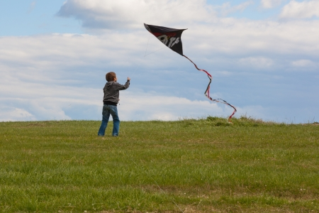 A boy flies his kite on a windy day  Meadow and some clouds on blue sky  Centraln view