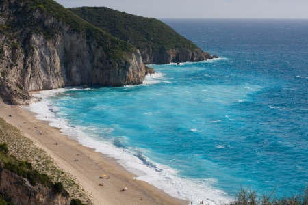 Blue water and beautiful beach on Lefkada island  Some people on the beach  High waves  Stock Photo